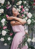 Young woman among roses in a garden. Girl with beautiful curly hair wearing pink dress among pink and red roses Royalty Free Stock Photo