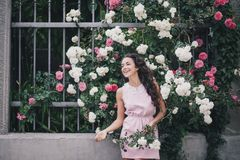 Young woman among roses in a garden. Girl with beautiful curly hair wearing pink dress among pink and red roses Royalty Free Stock Photos