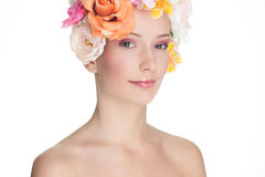 Young Woman with Roses on Head. Pretty, smiling young woman with a hat made of large fabric roses Royalty Free Stock Photography