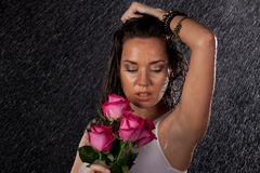 Young woman with roses under rain. Stock Images