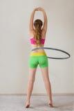Young woman rotating hula hoop Royalty Free Stock Image
