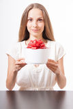 Young woman and round gift box on the table Stock Images