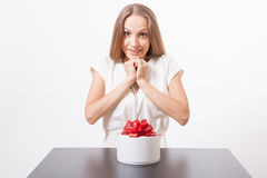 Young woman and round gift box on the table Royalty Free Stock Image