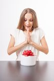 Young woman and round gift box on the table Royalty Free Stock Photography