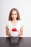 Young woman and round gift box on the table Stock Photos