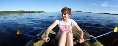 Young woman rowing boat on lake Stock Photo