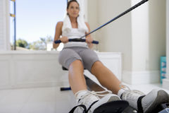 Young woman on rowing machine, low angle view. Young women on rowing machine, low angle view Stock Photography