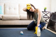 Tired housewife cleaning carpet. Young woman rubbing head wearing casuals and yellow gloves cleaning carpet with liquid soap Royalty Free Stock Image