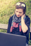 Young woman rubbing her neck while working on a laptop. Millenial working in a park Stock Images