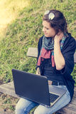 Young woman rubbing her neck while working on a laptop. Millenial working in a park Stock Photos