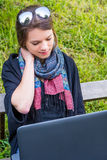Young woman rubbing her neck while working on a laptop. Millenial working in a park Royalty Free Stock Photo