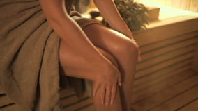 Young woman rubs his leg with oil in the sauna