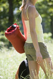Young woman, with rucksack and sleeping bag, standing in woodland clearing, departing on hiking trip, side view, mid-section Stock Photography