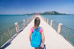 Young woman with rucksack. Travel and tourism. Young woman with rucksack walking on  jetty Royalty Free Stock Images