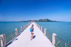 Young woman with rucksack. Travel and tourism. Young woman with rucksack walking on  jetty Royalty Free Stock Photography