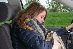 Young woman rummages while driving a car in her bag and is distracted royalty free stock image
