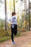 Young woman run in autumn the forest sunset lights. Young woman run in autumn the forest in sunset lights stock image