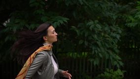 Young woman on the run, she is in a hurry. outdoors in summer. slow-motion stock footage