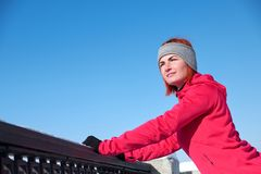 A young woman after a run rests on the waterfront and looks into royalty free stock image