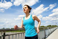 Young woman runing in the city over the brige in sun light. Royalty Free Stock Images