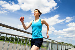 Young woman runing in the city over the brige in sun light. Royalty Free Stock Photos