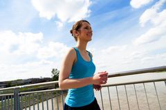 Young woman runing in the city over the brige in sun light. Stock Photography