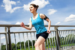 Young woman runing in the city over the brige in sun light, smil Stock Images
