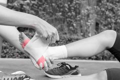 Young woman runner ankle being applied bandage by man in park. i Stock Images