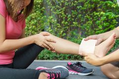 Young woman runner ankle being applied bandage by man in park. i Royalty Free Stock Photos