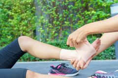 Young woman runner ankle being applied bandage by man in park. i Stock Photos