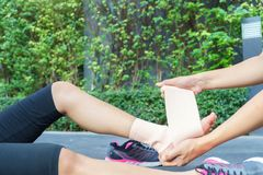 Young woman runner ankle being applied bandage by man in park. i Royalty Free Stock Image