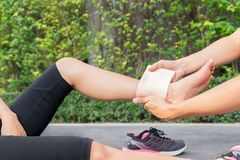 Young woman runner ankle being applied bandage by man in park. i Royalty Free Stock Photo