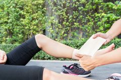 Young woman runner ankle being applied bandage by man in park. i royalty free stock photography