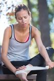 Young woman runner appling bandage after ankle injury Stock Image