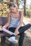 Young woman runner applying bandage to ankle Stock Image