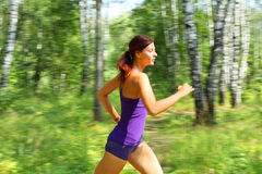 Young woman runner in a green forest Royalty Free Stock Photos