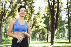 Woman runner is having break, drinking water. Young woman runner is having break, drinking water while jogging in park, copy space Stock Photography