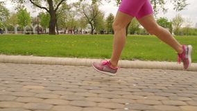 Young woman runner legs running on track. Slow motiom stock footage