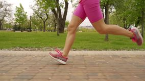 Young woman runner legs running on track. Slow motiom stock video