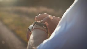 Young woman runner looking at sports smart watch, checking performance or heart rate pulse trace. Closeup of hands and. Wrist with smart watch screen stock footage