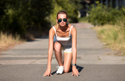 Young woman runner outdoor. Standing in start pose Stock Photo