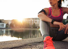 Young woman runner resting along pond. Young woman runner resting after workout session on sunny morning. Female fitness model sitting on street along pond in Royalty Free Stock Images