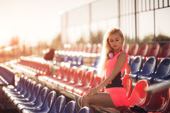Young woman runner resting after workout session on sunny morning. Stock Photos