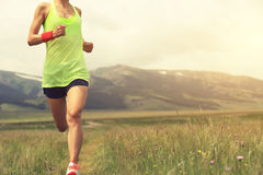 Young woman runner running on beautiful grassland trail Royalty Free Stock Images
