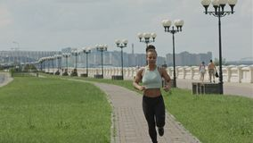 Young woman runner running on city bridge road. Professional shot in 4K resolution. 106. You can use it e.g. in your commercial video, business, presentation stock footage