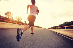 Young woman runner running. On city road Stock Images