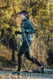Young woman runner running marathon walking sticks Royalty Free Stock Image