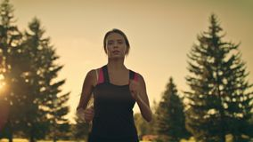Young woman runner running in park at sunset. Fitness woman jogging in park