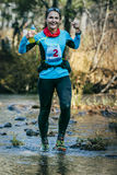 Young woman runner smiling while crossing a mountain river Stock Images