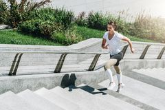 Young woman runner in sportswear runs up steps. Girl is doing sports exercises in city. Sports, training, workout. Summer sunny day. Young woman runner in Stock Photography